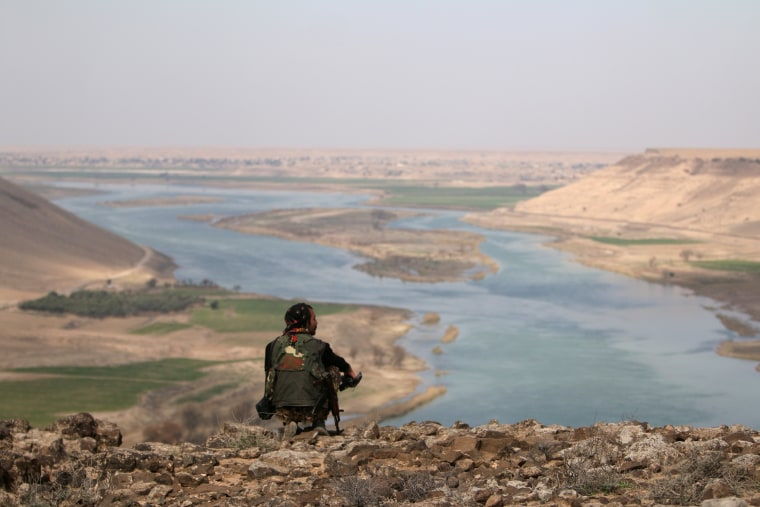 Image: A Syrian Democratic Forces (SDF) fighter rests while looking over the Euphrates River north of Raqqa.