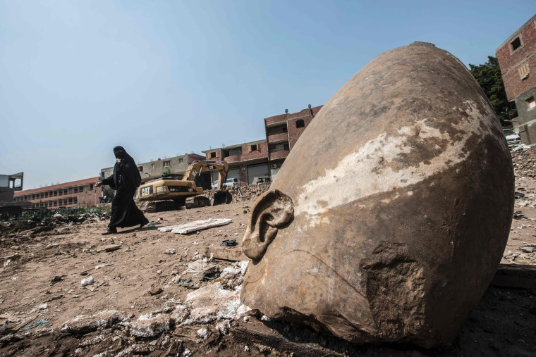 Image: An Egyptian woman walks past the head of a statue at the site of a new discovery by a team of German-Egyptian archeologists in Cairo's Mattarya district