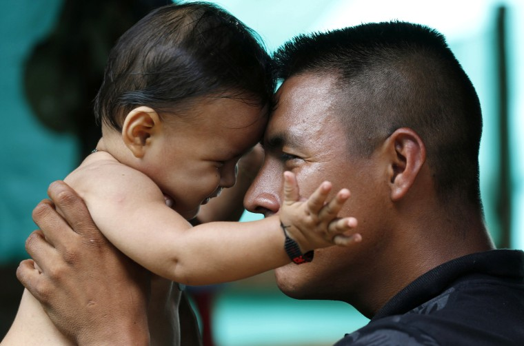 Image: FARC rebel Vicente Pulecio plays with his 9-month-old son Dainer