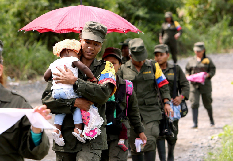 Image: Guerrilla women from Revolutionary Armed Forces of Colombia (FARC), walk with their children from their transitory camp to a rural site