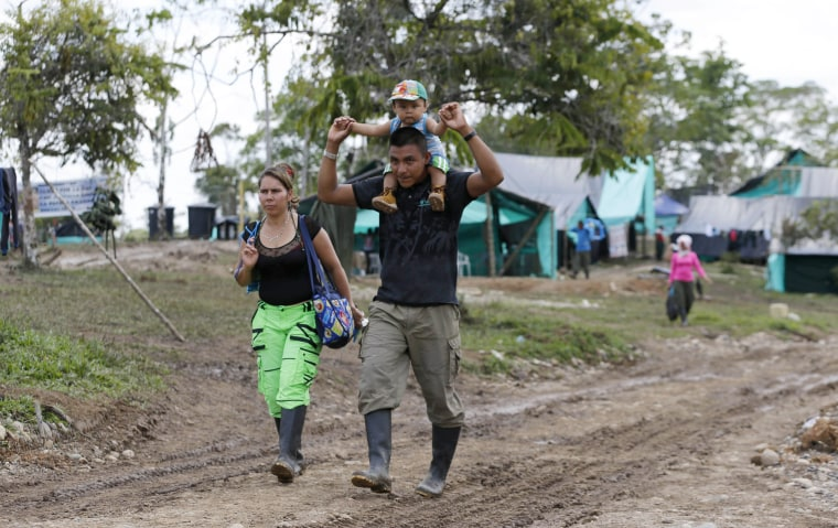 Image: FARC rebel couple Jerly Suarez, left, and Vicente Pulecio walk to a cooking class with their 9-month-old son Dainer at a rebel camp