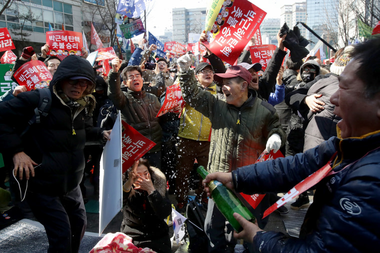 Image: South Koreans celebrate after hearing the Constitutional Court's verdict on March 10, 2017 in Seoul.