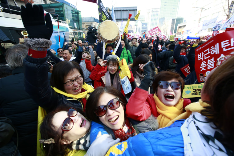 Image: South Koreans cheer after the court's ruling on the impeachment of President Park Geun-hye near the Constitutional Court.