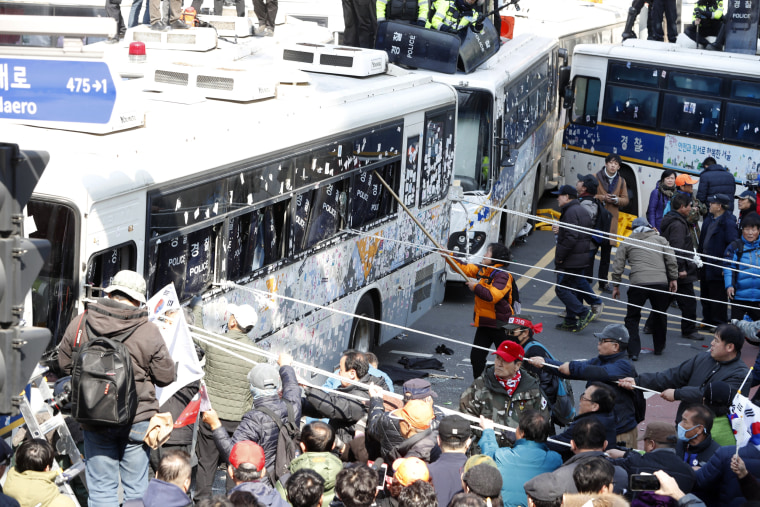 Image: Supporters of the president clash with policemen as they attempt to pass the barricade of police buses towards the Constitutional Court in protest after the court's ruling.