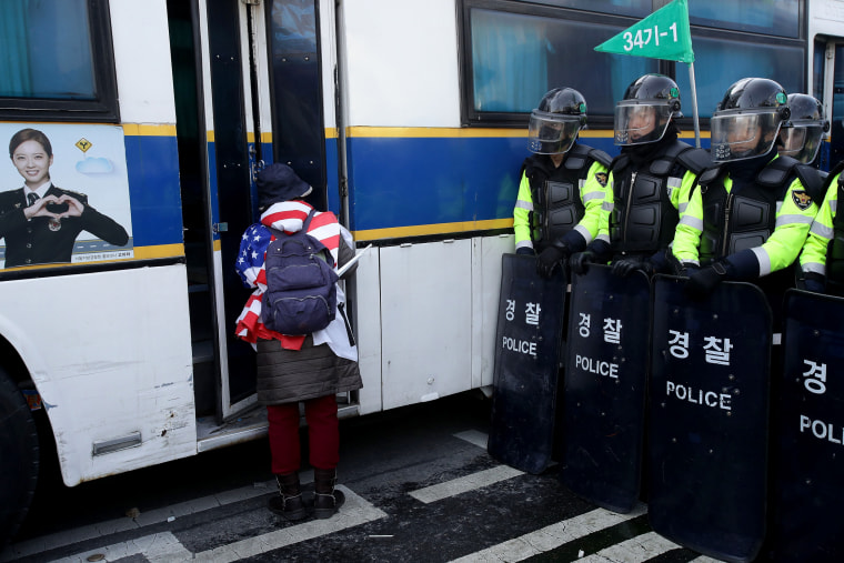 Image: A supporter of the South Korean president looks at a police bus during a protest against the court's ruling.