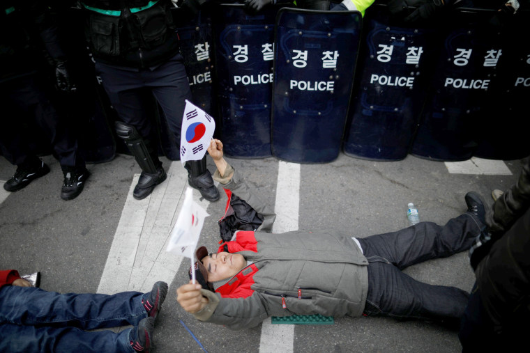 Image: A supporter of the former president lies in front of a barricade of riot police during a protest after Park's impeachment was accepted.