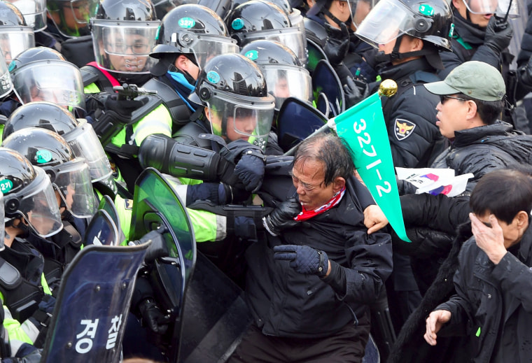Image: Supporters of Park Geun-hye clash with police after the announcement of the Constitutional Court. The rival crowds outside South Korea's court show the opposing passions and generational splits over the country's sweeping political scandal.