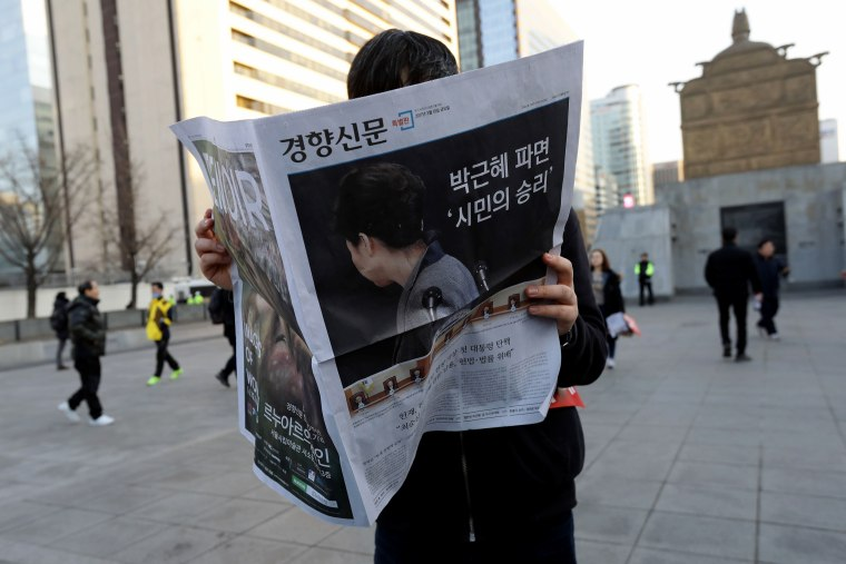 Image: A South Korean man reads an extra edition newspaper reporting on the impeachment of President Park Geun-hye.