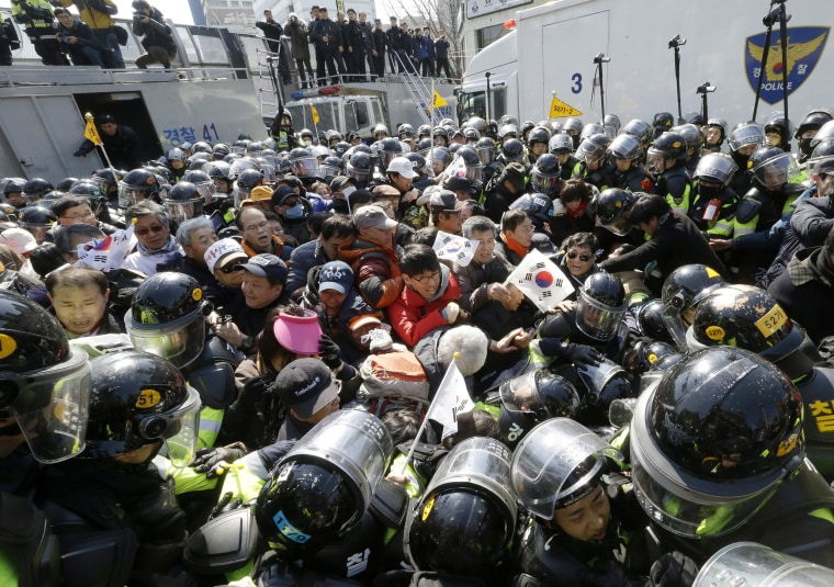 Image: Supporters of president are blocked by police officers as they march toward Constitutional Court.