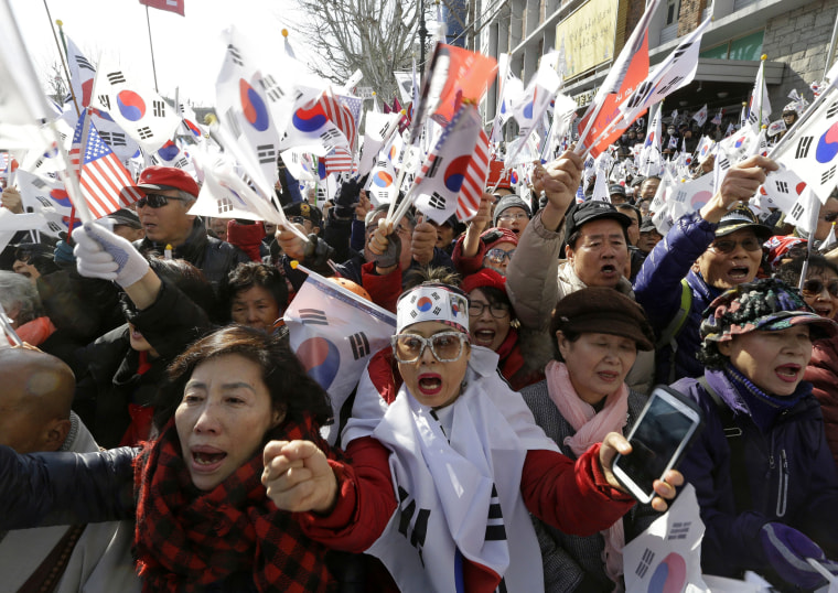Image: Supporters of South Korean President Park Geun-hye shout slogans during a rally opposing her impeachment.