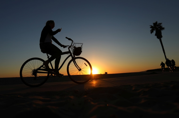 Image: A woman looks at her phone as she rides her bike along the boardwalk in Venice Beach