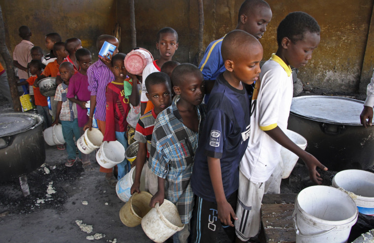 Image: Displaced Somali boys who fled the drought in southern Somalia stand in a queue to receive food handouts at a feeding center in a camp in Mogadishu, Somalia.