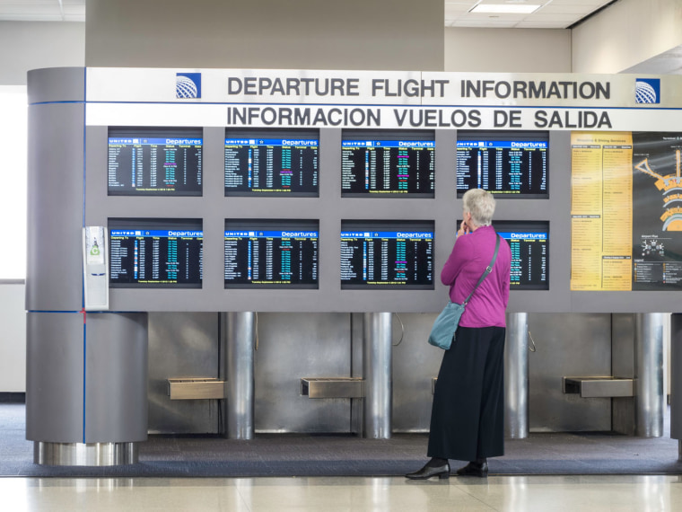 Image: Bilingual Departure Flight Information Board and Passenger, Newark Liberty International Airport, Newark, New Jersey, USA. Image shot 2012.
