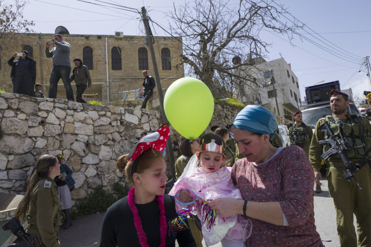 Image: A Palestinian family watches from their house as Jews pass by, guarded by Israeli soldiers, during the annual Purim parade in the West Bank city of Hebron.