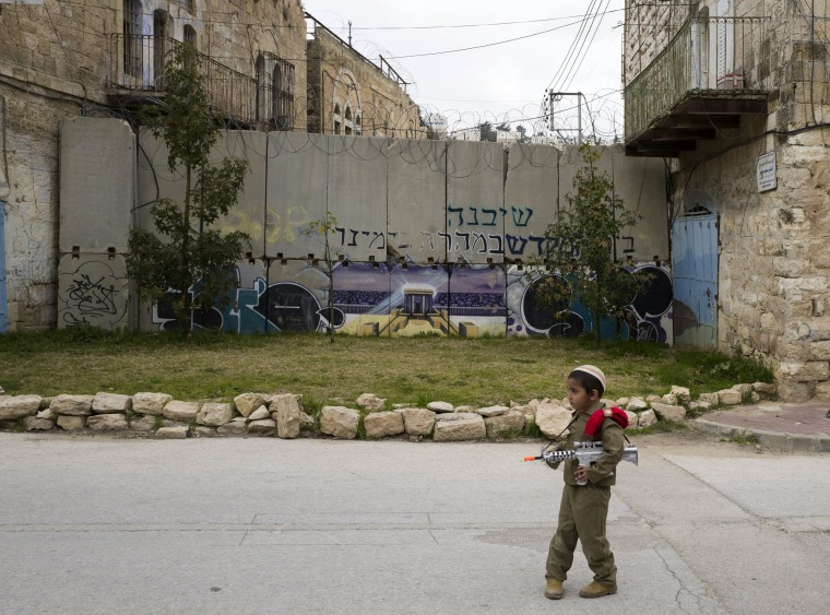 Image: A young Jewish boy dressed in an army costumes stops before a separation wall blocking a street during the annual Purim parade in Hebron.
