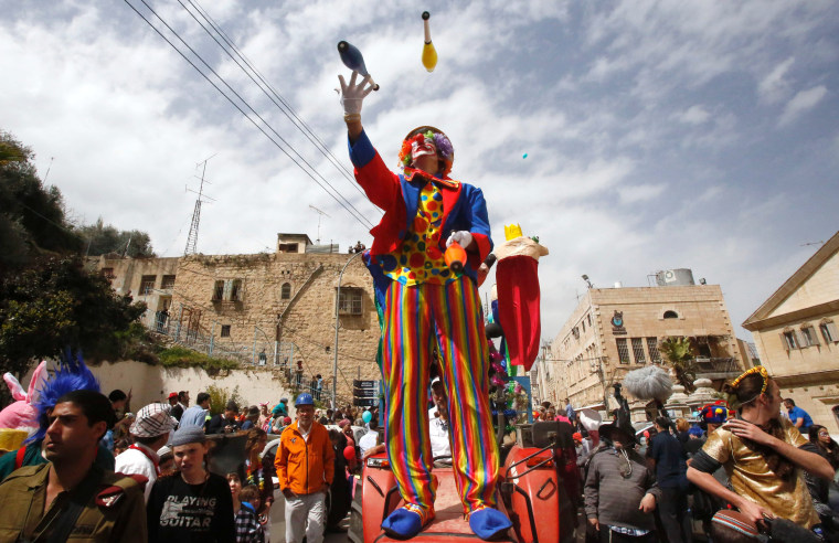 Image: Israeli settlers take part in a parade to celebrate the Jewish holiday of Purim on al-Shuhada Street, in the West Bank town of Hebron.