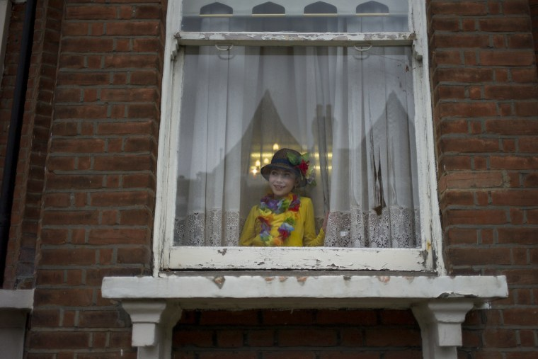 Image: A young Jewish girl looks from a window during celebrations of Purim in London. Purim is celebrated by Jewish communities around the world with parades and costume parties.