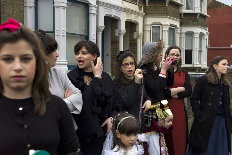 Image: Jewish women watch as men dance down the street during Purim in London.