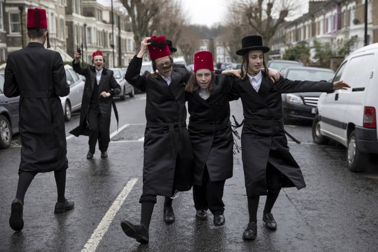 Image: Young Jewish men dance down the street during the annual Jewish holiday of Purim in London.