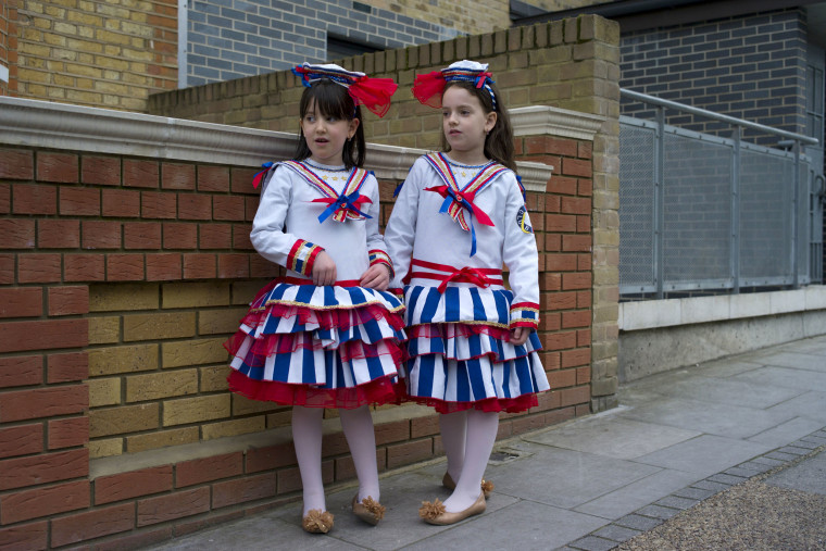 Image: Young girls stand outside a home during Purim celebrations in London, England.