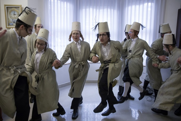Image: Young Jewish men dance around a local business man's home during the Jewish holiday of Purim in London.