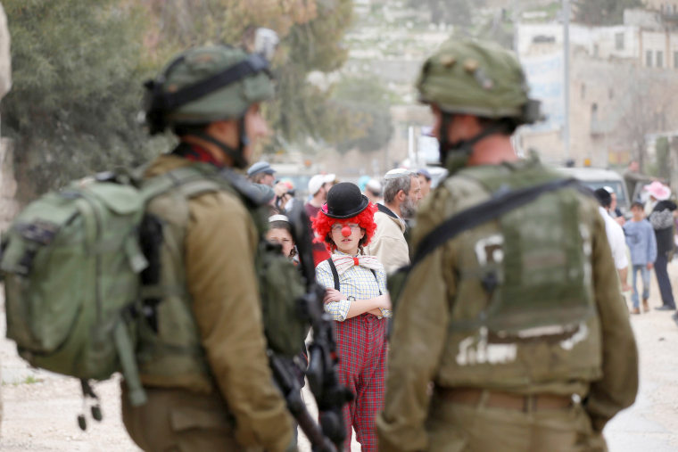 Image: A boy dressed in costume takes part in a parade in the West Bank city of Hebron.
