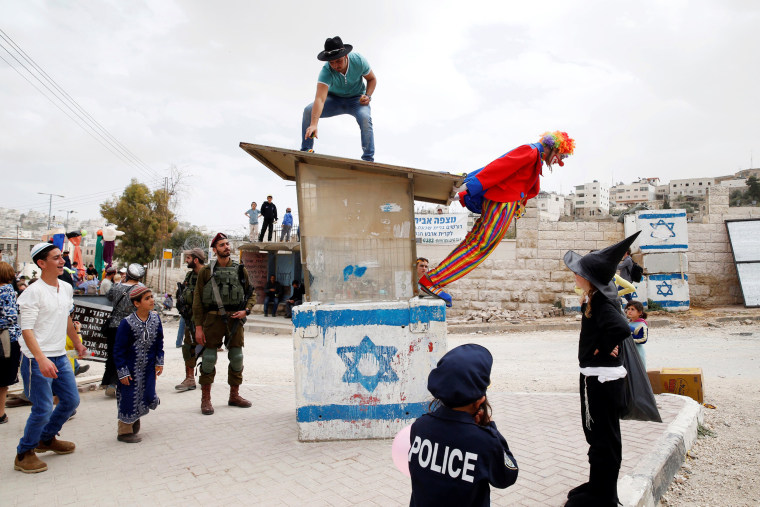 Image: An Israeli soldier secures a parade marking the Jewish holiday of Purim.