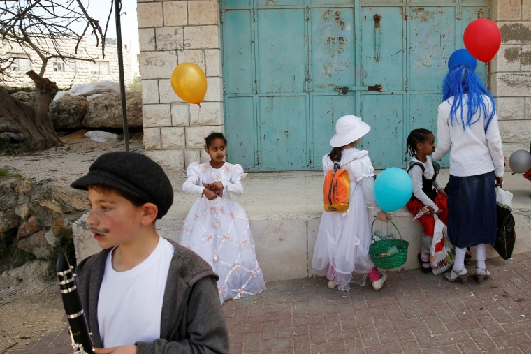 Image: People dressed in costumes take part in a parade marking the Jewish holiday of Purim, a celebration of the Jews' salvation from genocide in ancient Persia, as recounted in the Book of Esther, in the West Bank city of Hebron, March 12, 2017.