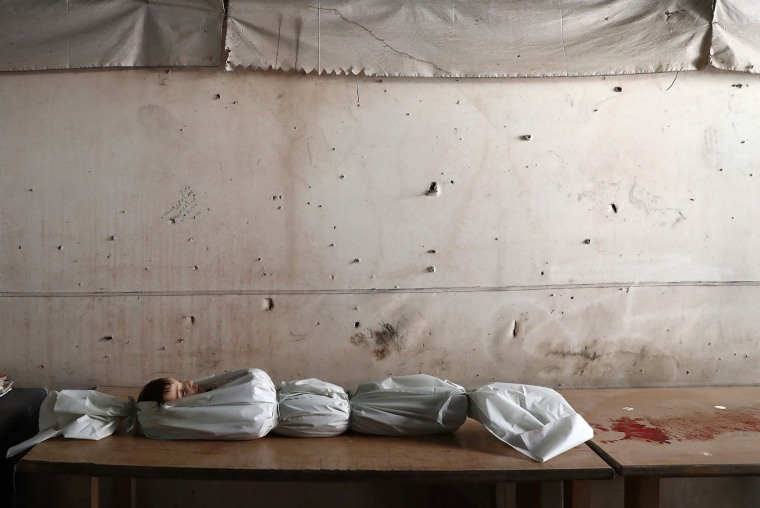 Image: The body of a Syrian child lies on a table at a morgue following reported air strikes on the rebel-held town of Douma