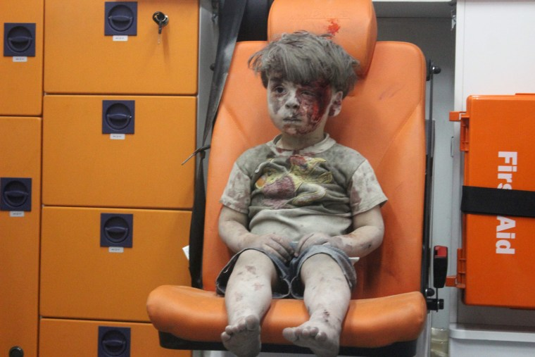 Image: Omran, a four-year-old Syrian boy covered in dust and blood, sits in an ambulance after being rescued from the rubble of a building hit by an air strike