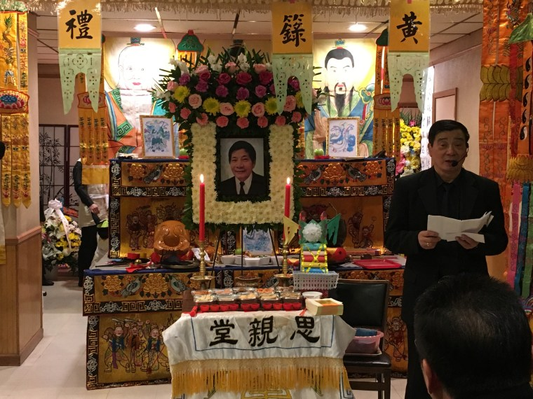 A funeral services officiator speaks in Fukienese, a dialect of Chinese, to friends and family who gathered in Manhattan Sunday to say goodbye to Jiansheng Chen, who died after being shot in Virginia by a security guard.