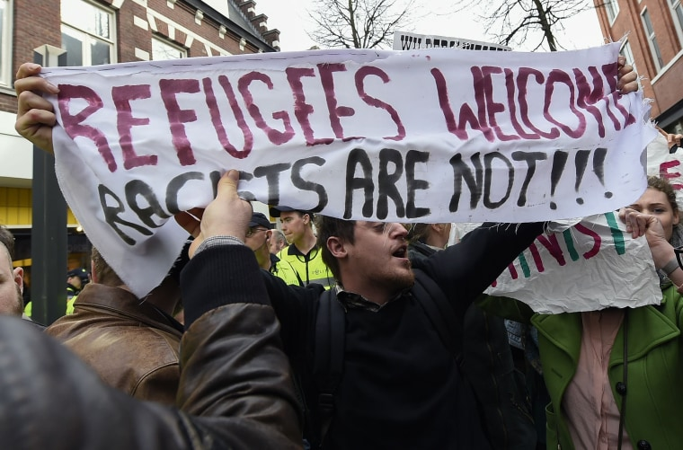 "Image: A protester with a banner reading ""Refugees welcome, racists are"
