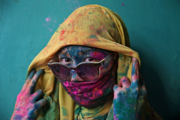 Image: A woman poses for a photograph during Holi celebrations in the town of Barsana in the state of Uttar Pradesh