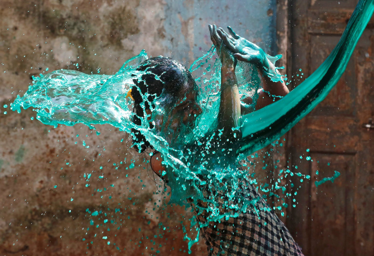 Image: A girl reacts as coloured water is thrown on her face while celebrating Holi, the Festival of Colours, in Mumbai