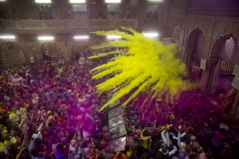 Image: Hindu devotees throw colored powder on each other inside Banke Bihari temple during Holi festival celebrations