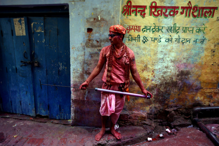 Image: A Hindu devotee holds a water gun as he takes part in the religious festival of Holi in Nandgaon
