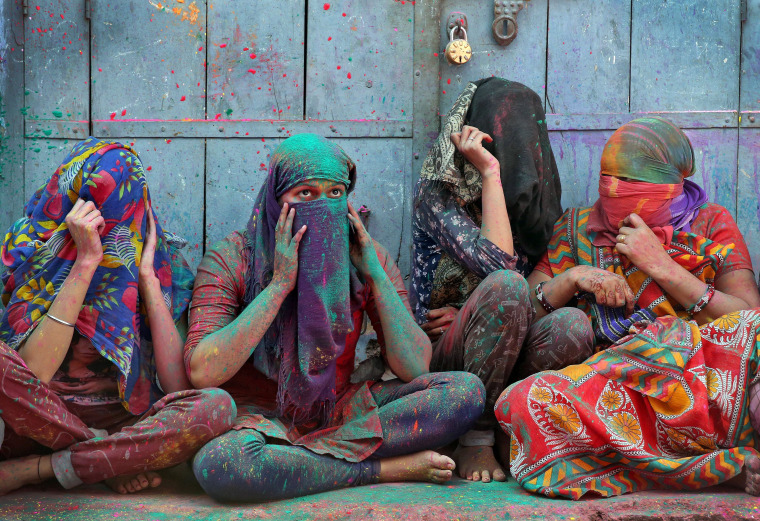 Image: Women cover their faces during Holi celebrations in the town of Barsana in the state of Uttar Pradesh