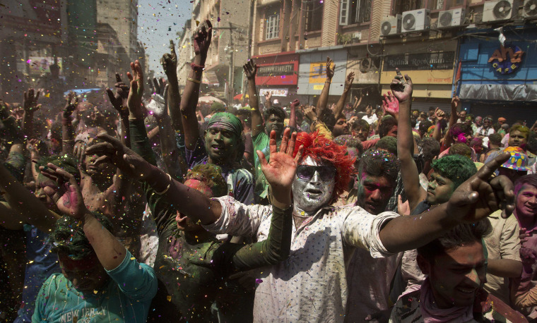 Image: Indians with faces smeared in color dance during the Holi celebrations