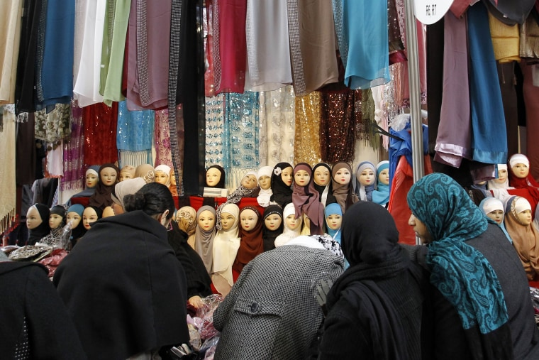 Image: Women look at veils on display