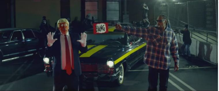 Rapper Snoop Dogg pretends to shoot a clown dressed as Donald Trump