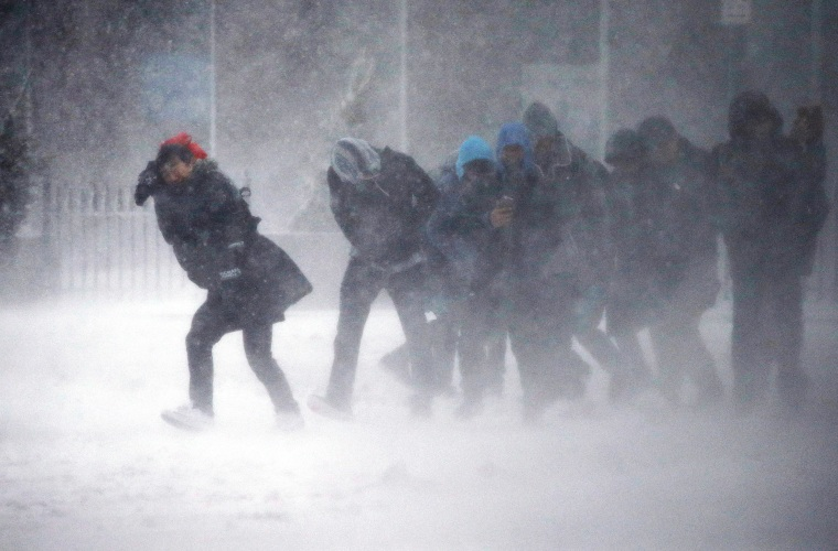 Image: People struggle to walk in the blowing snow during a winter storm in Boston