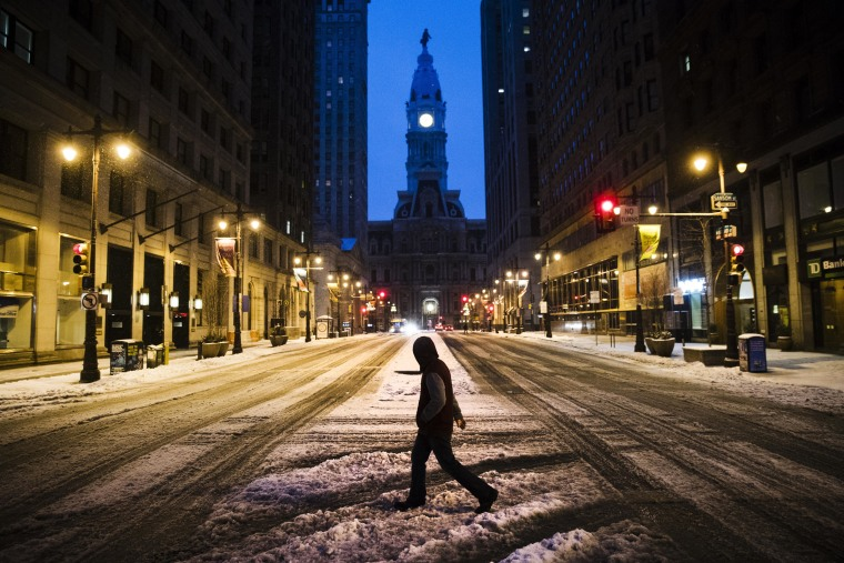 Image: A man crosses South Broad Street in view of City Hall during a winter storm in Philadelphia