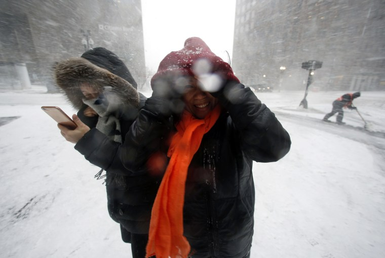 Image: People walk in the wind-driven snow during a winter storm