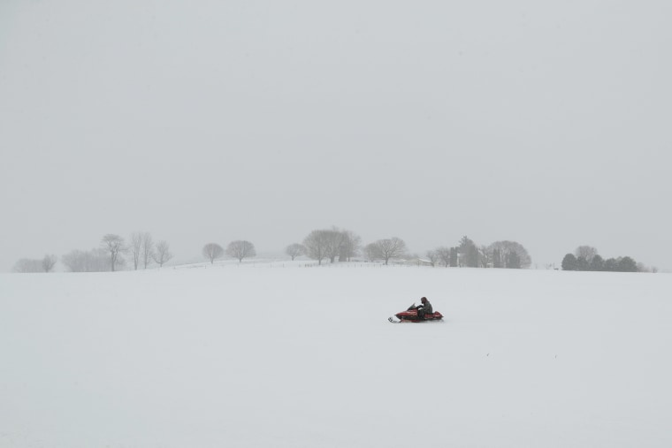 Image: A person rides a snowmobile through a field in Gap, Pa.
