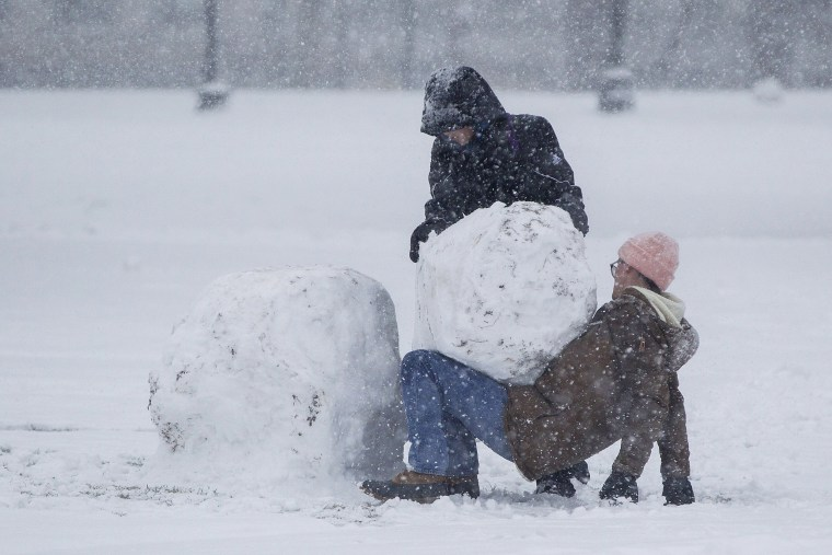 Image: Two people work to build a snowman on the Boston Common