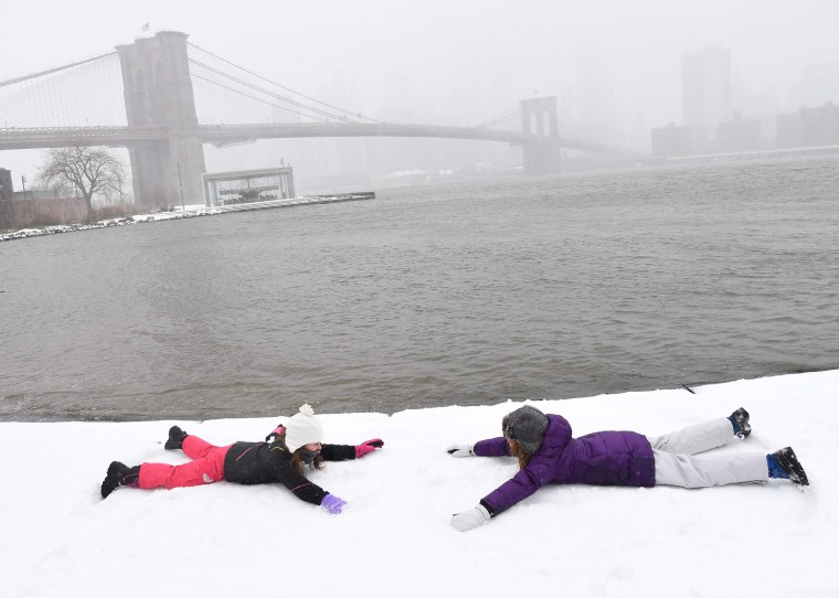 Image: Two girls make snow angels in Brooklyn Bridge Park