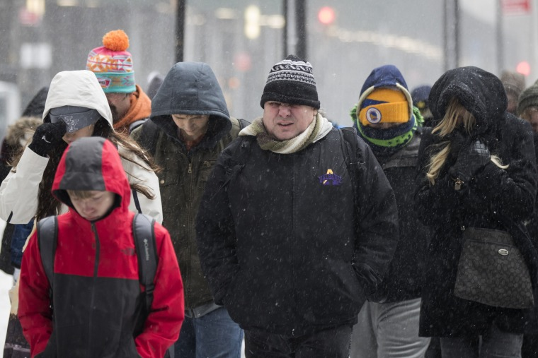 Image: A tourist group walks through the snow and wintry mix in New York