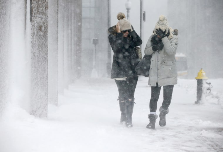 Image: Two women struggle to walk in the blowing snow during a winter storm