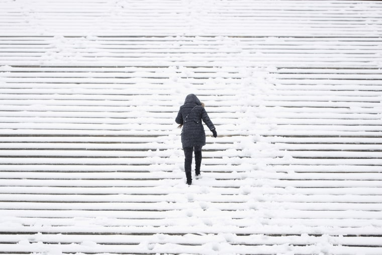 Image: A woman climbs the snow covered steps of the Philadelphia Museum of Art