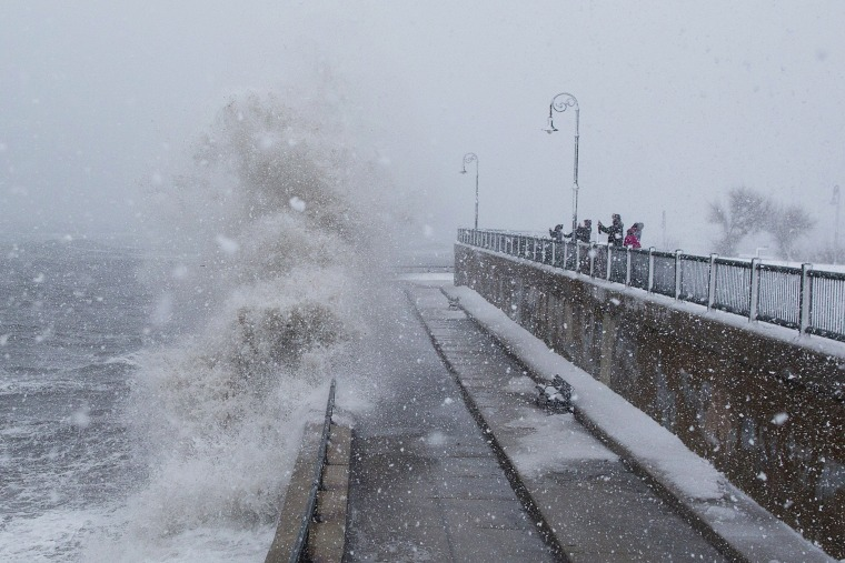Image: People watch as waves crash over the seawall along Lynn Shore Drive
